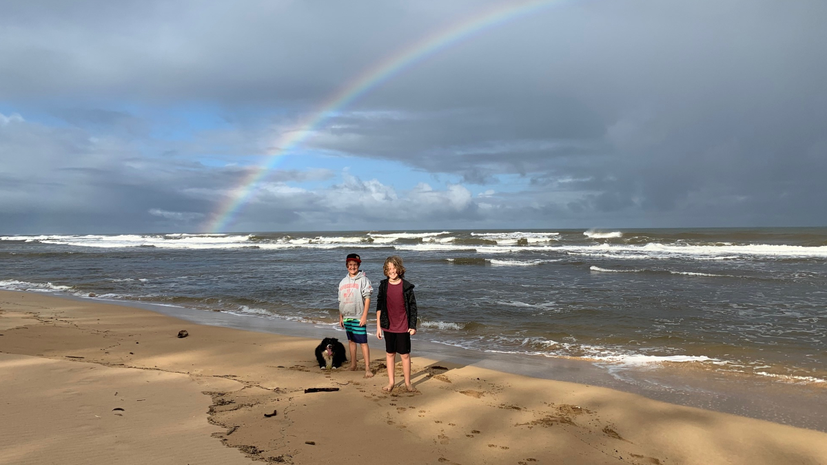 learners at beach with a rainbow behind them